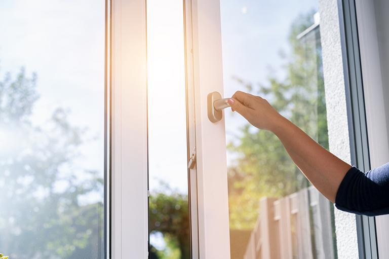 Osoba otwiera okno